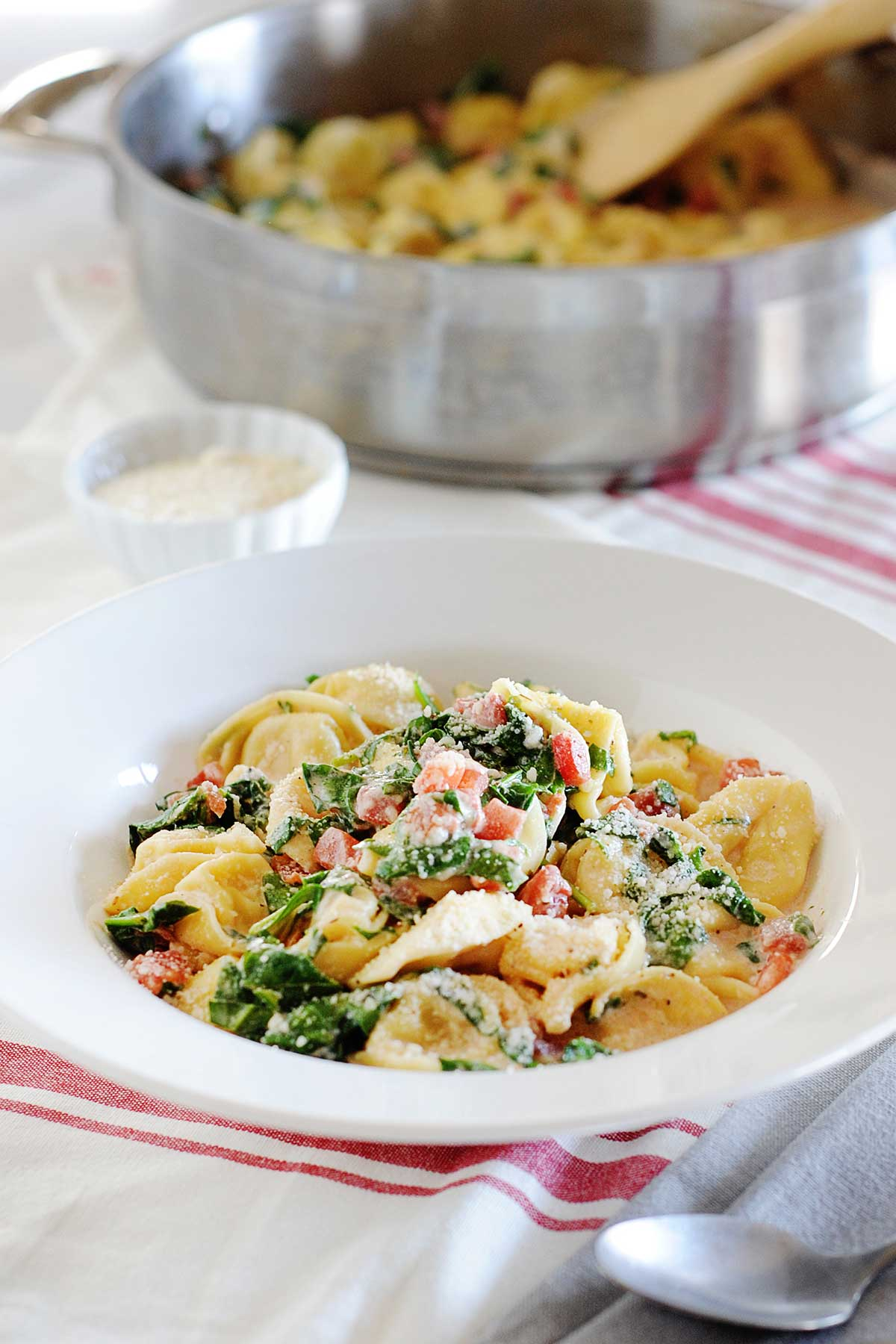large bowl of spinach tortellini with large skillet of the same in the background of image