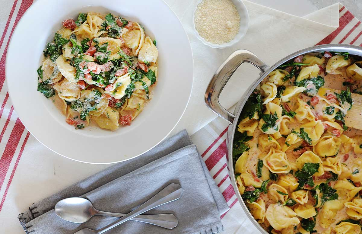 overhead view of spinach tortellini in a bowl and skillet