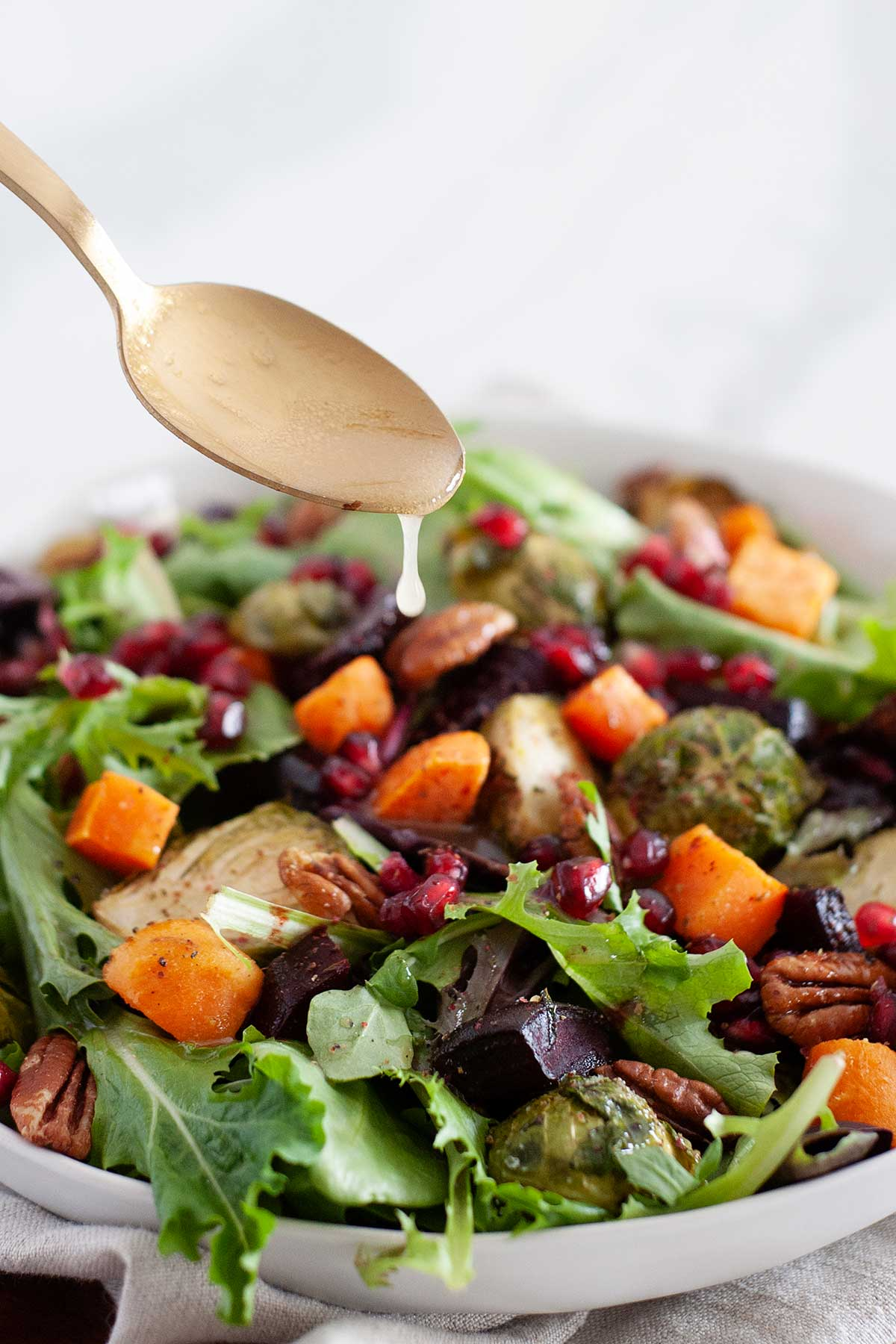 pouring dressing over winter salad with a spoon