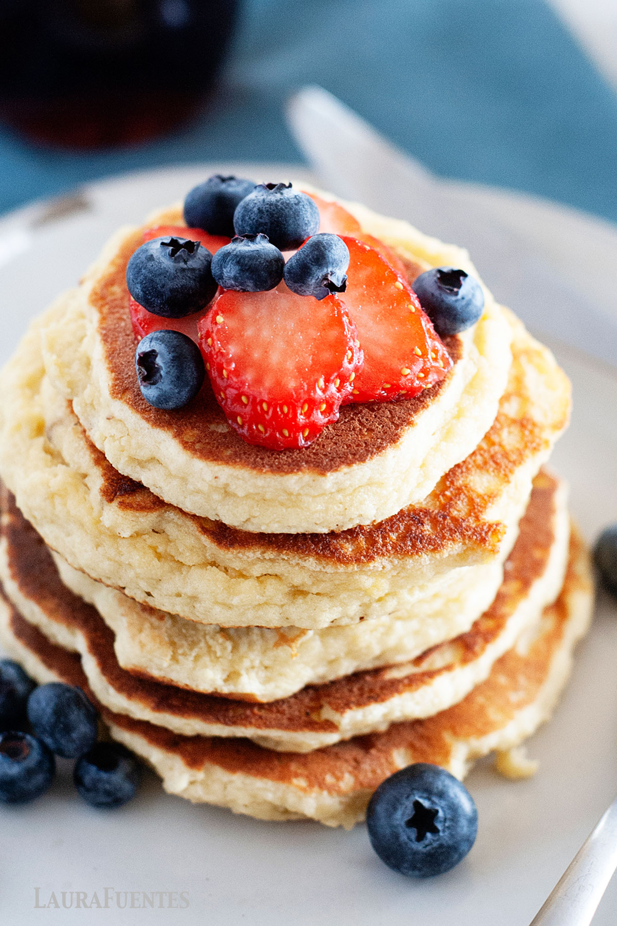 stack of almond flour pancakes topped with strawberries and blueberries