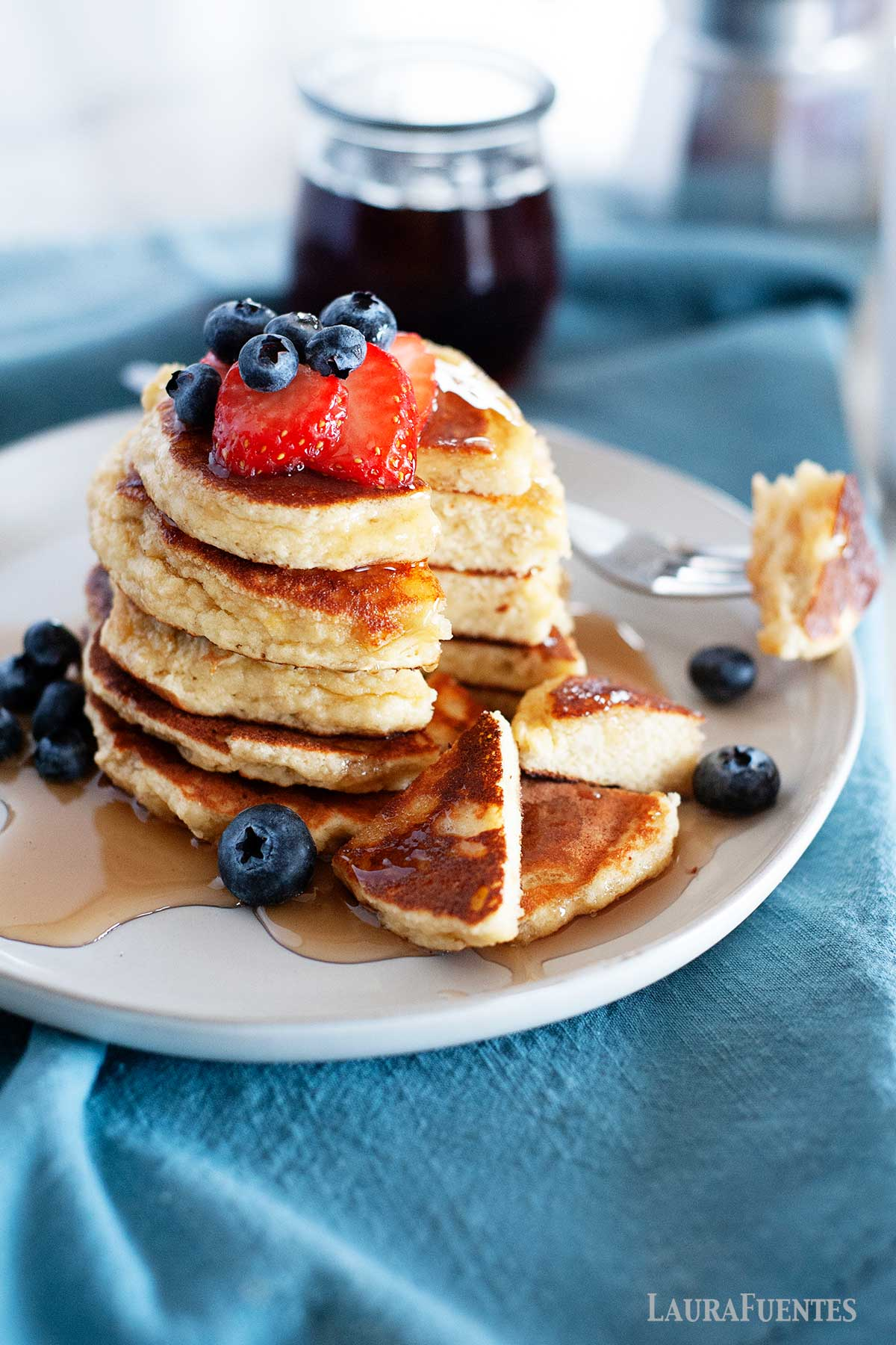 large stack of almond flour pancakes topped with fruit and with a bottle of syrup in the background