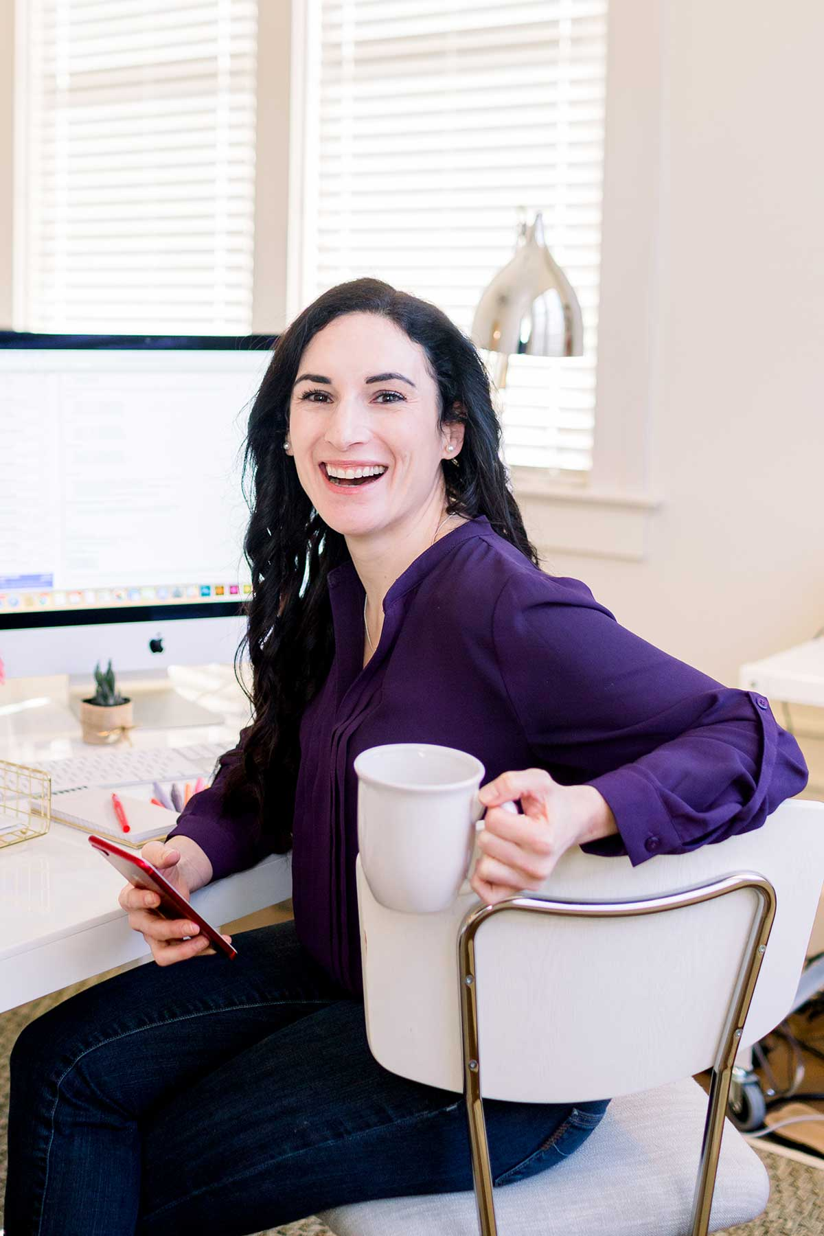 woman sitting at desk with phone and coffee cup in hand
