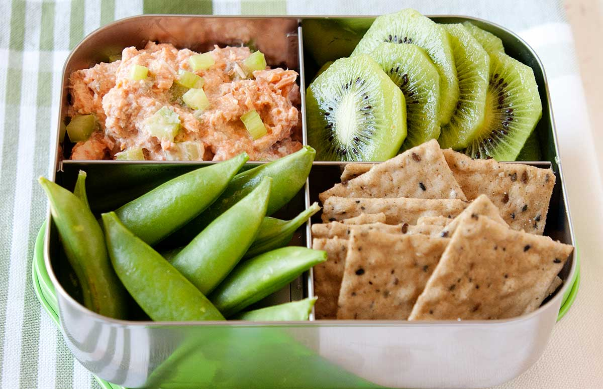 salmon salad packed in a bento box with crackers fruit and veggies