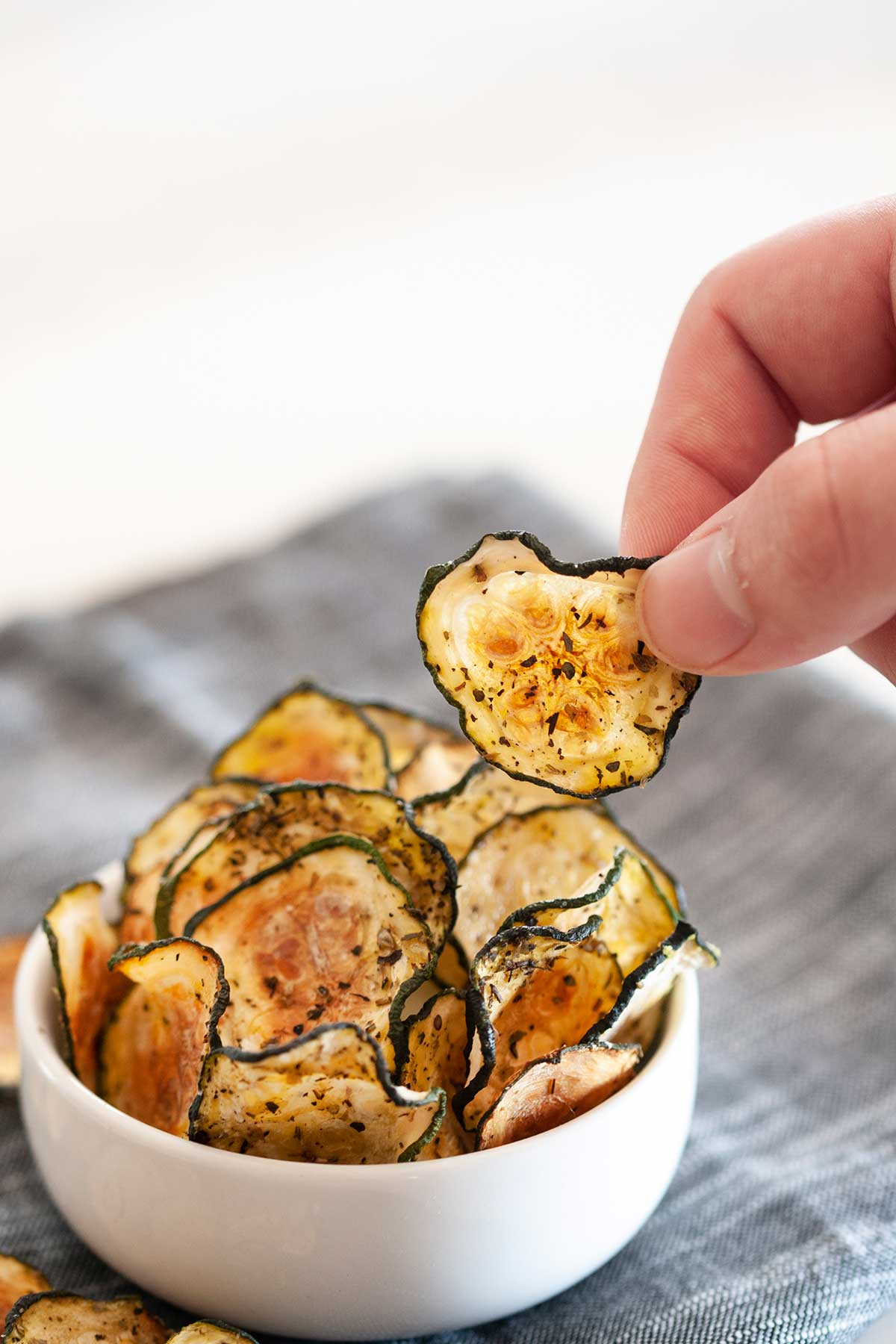 hand grabbing a zucchini chip from a bowl