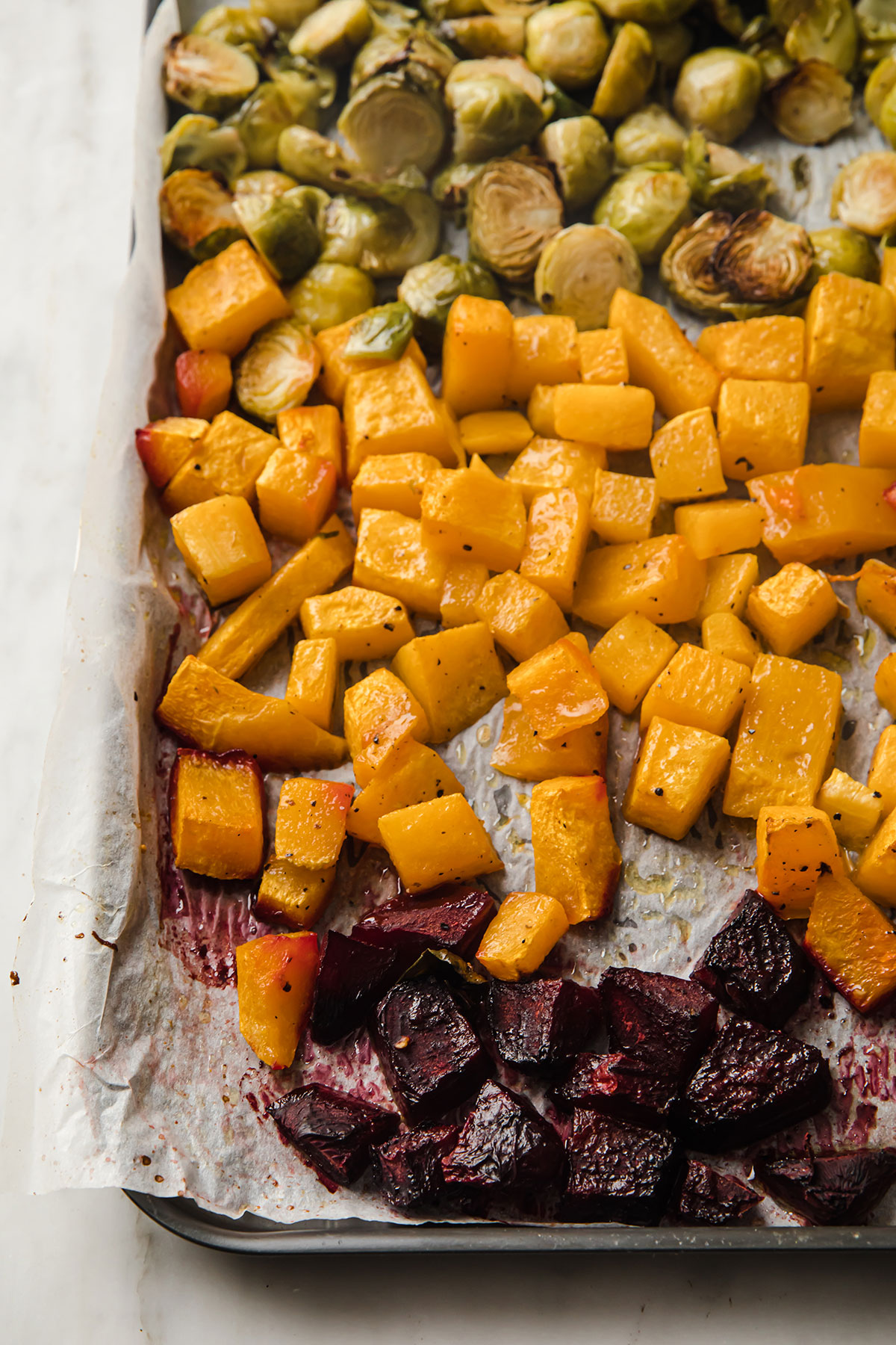 part of a baking sheet filled with chopped beets, butternut squash and halved Brussels sprouts, all roasted.