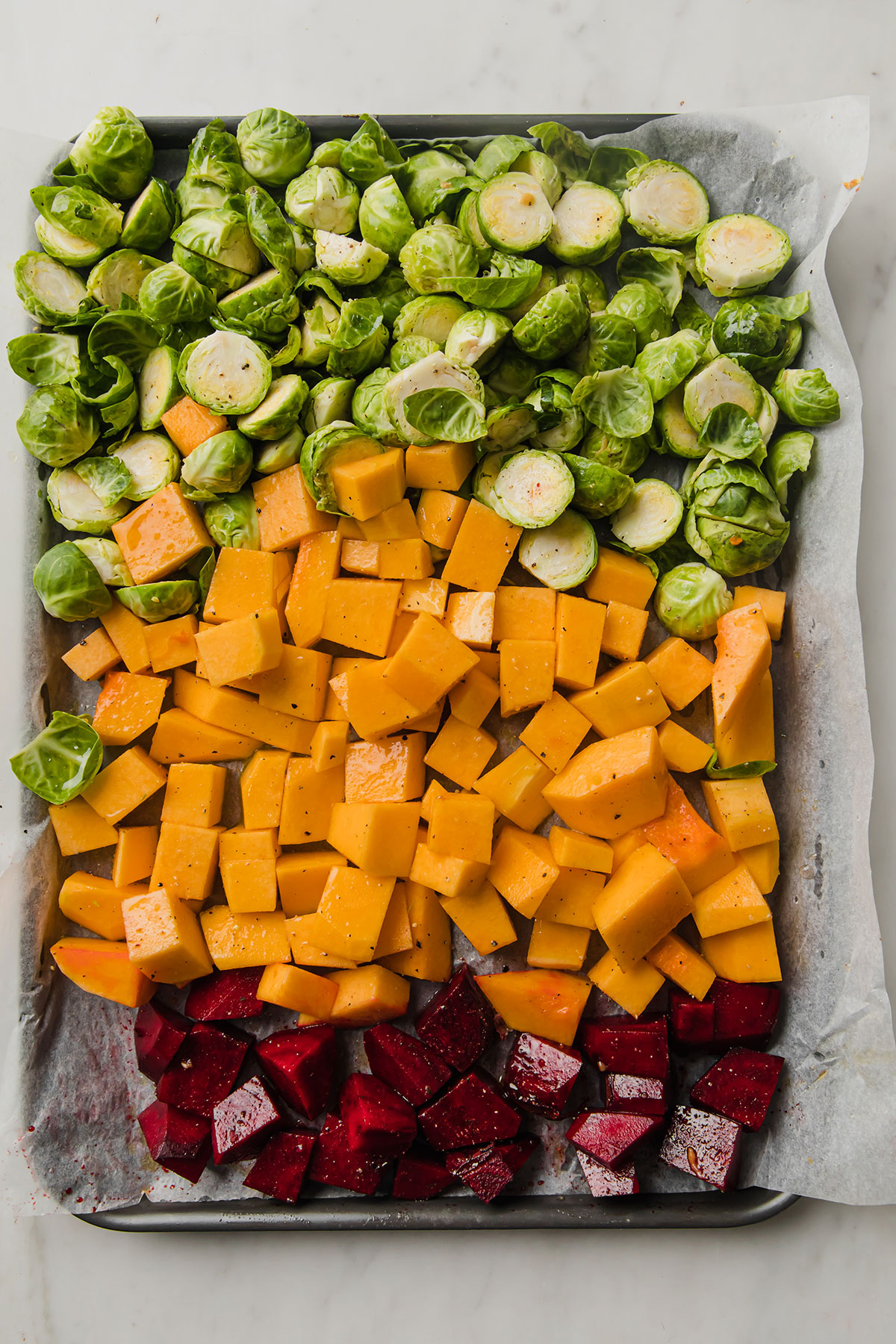 large baking sheet topped with chopped Fall vegetables arranged in three rows